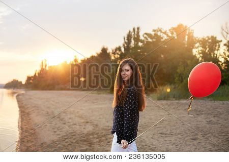 Portrait Of Young Woman With Red Air Balloon And Present Bag Near The Calm Sea Or Lake. Girl On Her