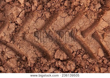 Traces Of Tractor Wheels On Brown Soil.