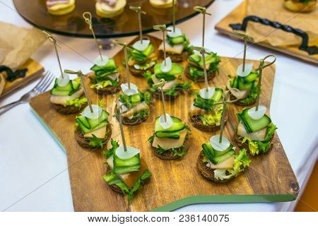 Canape With Salted Lard, Onion, Cucumber, Rye Bread And Parsley. Catering Banquet Table With Differe