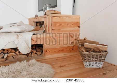 Fragment Of The Interior Of A Country House. Wooden Bed And Firewood Under It, Basket Full Of Firewo