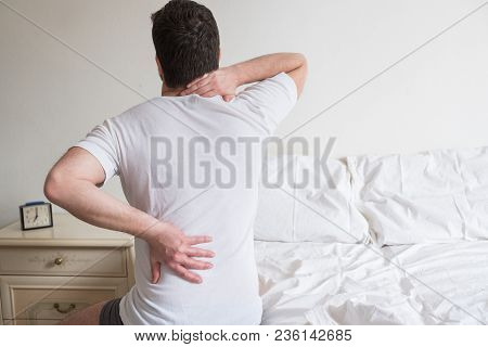 Man Suffering From Backache Getting Out Of Bed