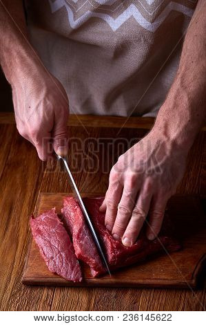Strong Professional Man's Hands Cutting Raw Beefsteak, Selective Focus, Close-up