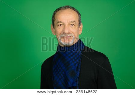 Good-looking Handsome Senior Gray-haired Man With Well-trimmed Beard In Black Sweater And Blue Chequ