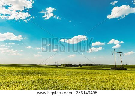 Air Line Supports. Steel Overhead Transmission Line Masts In A Green Meadow With Sunny Blue Sky. Wid