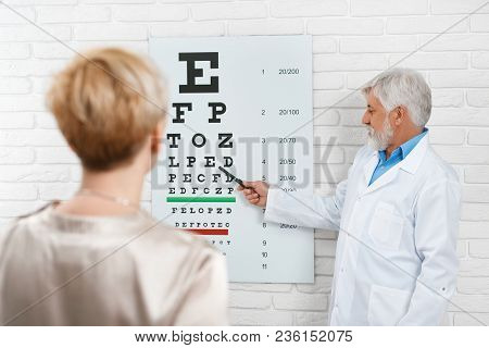 Old Ophthalmologist Is Cheking Patient's Vision.
