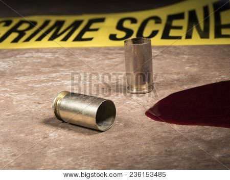 Pistol Brass And Blood On A Tan Tile With Police Tape Behind