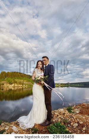 Beautiful Couple In Love Kissing While Standing On Ground By Lake. Wedding Couple At Sunset, Blue Cl