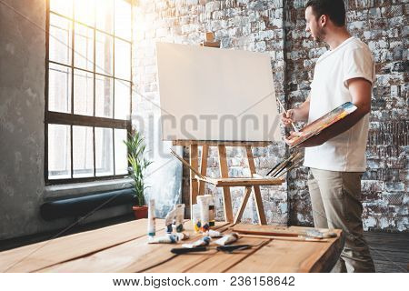 Man Artist Stands In Front Of A Blank Canvas On Easel With Palette In Loft Art Studio. Male Painter