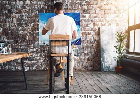 Male Painter Sits On Chair In Front Canvas And Drawing Picture In Studio. Art Class And Workshop. Ar