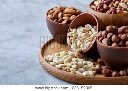Mixed Nuts In Brown Bowls On Wooden Tray Over White Background, Close-up, Top View, Selective Focus.