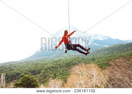 A Woman Is Hanging On A Rope.