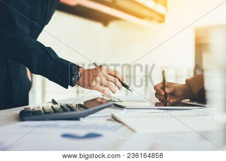Two Business People Working Together On Desk In Office Room.