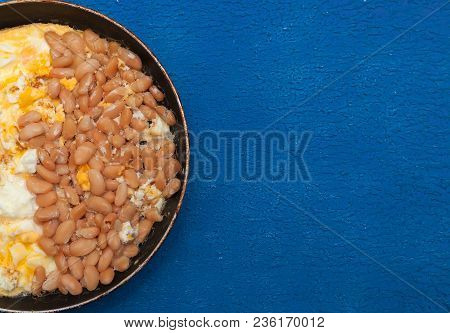 Large Pink Fried Beans And Scrambled Egg Closeup In The Pan On A Blue Textured Background.