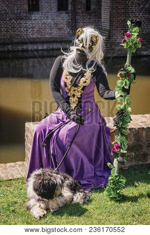 April  19, 2014, Haarzuilens, The Netherlands: Catwoman With Dog And Staff Sitting On A Wall Of The