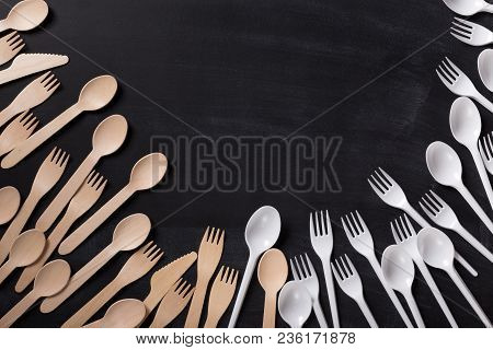 Organic Bamboo Disposable Cutlery Vs Plastic Ones On Black Background. Environmentally Friendly Wood