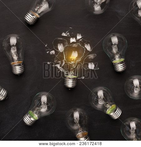 One Broken Glowing Light Bulb Among Whole Ones On Black Background, Top View. Creativity, Idea And F
