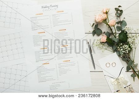 Wedding Background With Checklist. Paper Planner And Wedding Rings On White Wooden Table With Tender