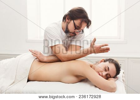 Male Masseur Massaging Female Back And Shoulders. Professional Body Treatment Or Relaxation Procedur