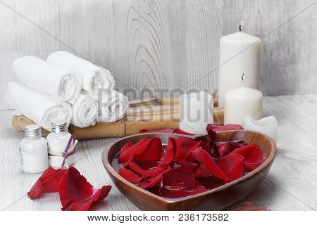 Red Rose Petals In The Water Next To A White Set For Spa Procedures For The Skin Of The Hands