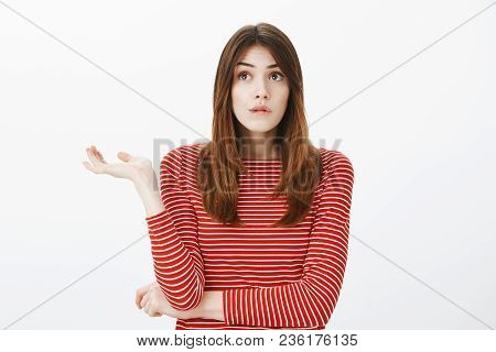 Girl Tangle In Thoughts. Portrait Of Clueless Troubled European Female Student In Striped Red Blouse