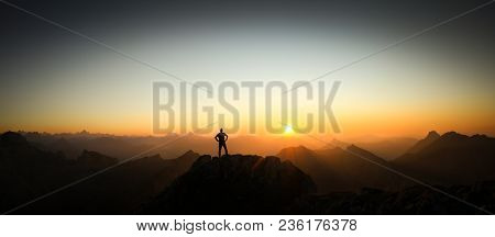 Happy Winning Success Man At Sunset Or Sunrise Standing Relaxed On Mountain Peak. Climbing And Hikin