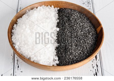 Two Kinds Of Salt. White Sea Salt And Black Himalayan Salt In A Wooden Bowl On White Background.