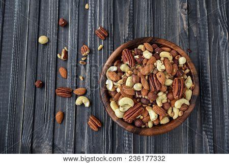 Nuts Mix Almonds, Cashews, Macadamia, Peanuts, Walnuts, Pecans, Pine Nuts, Pistachios In A Wooden Pl