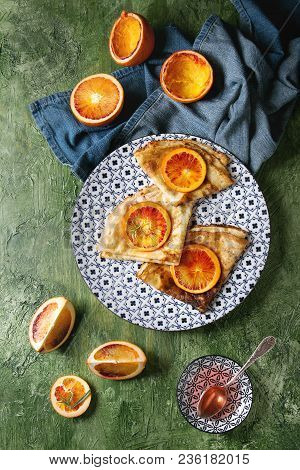 Homemade Crepes Pancakes Served In White Decorate Ceramic Plate With Bloody Oranges And Rosemary Syr