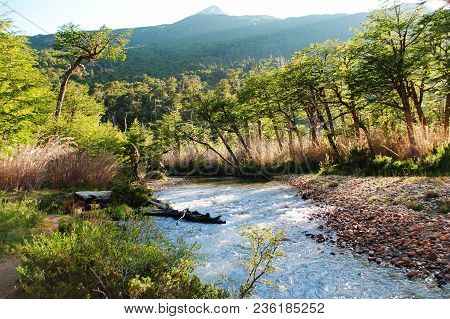 Beautiful Valley With A River And A Mountain Surrounded By Trees, In The Morning Or The Afternoon, W