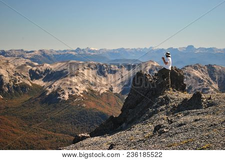 Man Taking A Photograph At The Top Of A Mountain After A Hike, With A Panoramic View Of The Andes In