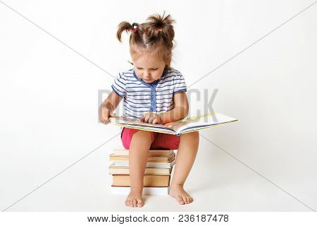 Curious Female Child With Two Funny Pony Tails, Sits On Pile Of Books, Reads Interesting Faity Tale,