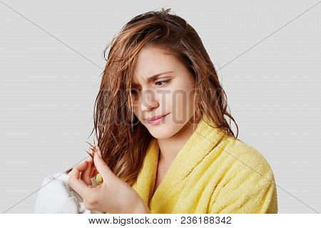 Displeased Female Looks At Wet Wiry Hair, Being Dissatisfied With Shampoo, Has Split Ends, Wears Bat