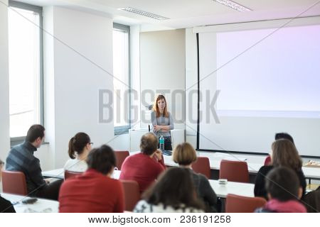 Female Speaker Giving Presentation In Lecture Hall At University Workshop. Audience In Conference Ro