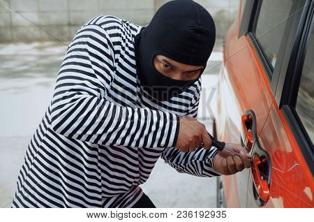Thief In Black And White Jacket Using Screwdriver To Open Car Door To Stealing A Car On Street In Bi