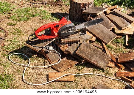 Electric Saws And Chainsaw. Electric Saw Chain On The Background Of Sawn Timber. The Concept Of Proc