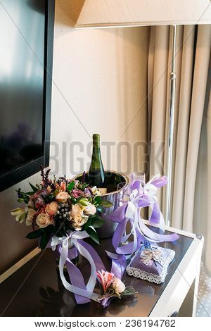 A Wedding Bouquet, A Boutonniere, A Bottle Of Champagne Are On The Table