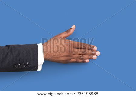 African-american Businessmans Hand Ready For Handshake Isolated On Blue Background. Man Inviting By