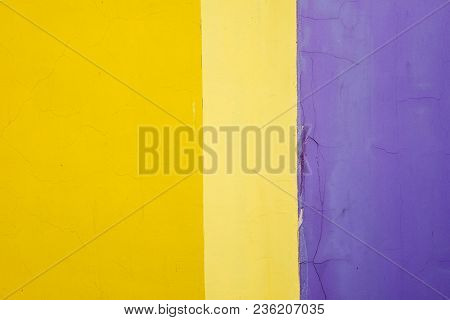 Multicolored Wall With Cracks. The Wall Consists Of Three Colors - Bright Yellow, Pale Yellow And Pu
