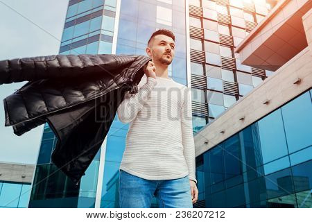 Arabian Man Holding His Coat And Walking In City Center. Young Man Throws Coat On Shoulder. Fashion