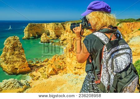 Travel Photographer Takes Shot Of Iconic Natural Arches Of Praia Da Marinha In Algarve. Female Touri