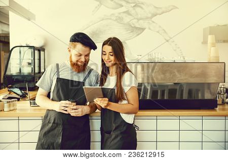 Coffee Business Concept - Positive Young Bearded Man And Beautiful Attractive Lady Barista Couple In