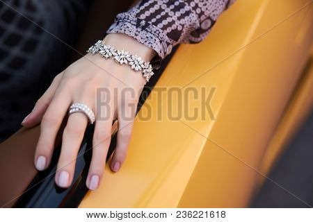 Beautiful Woman With Yellow Sport Car. Young Female Model With Lixury Diamonds Jewerly Sitting In A