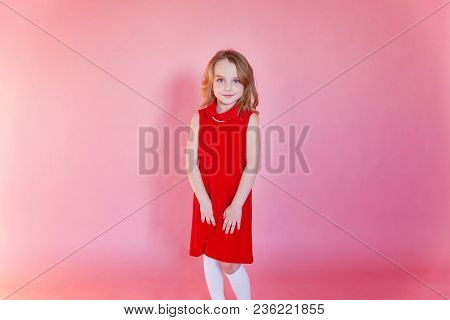 Little Cute Sweet Smiling Girl In Red Dress Standing On Pink Colourful Pastel Trendy Modern Fashion