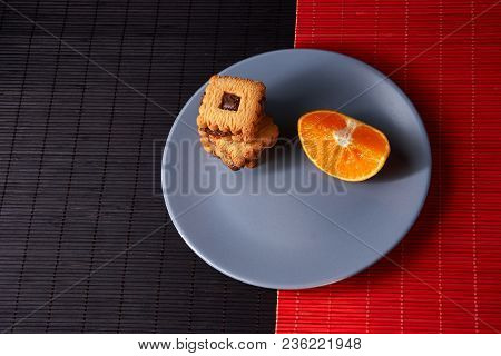 Chocolate Chip Cookies And Piece Of Orange On Plate And On Red And Black Background With Place For T