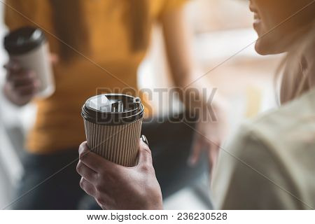 Glad lady holding caffeinated beverage in her hand. Focus on paper mug poster