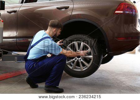 Mechanic changing car wheel in garage. Tire service