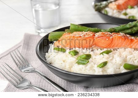Fish fillet served with rice, green beans and asparagus sticks in bowl