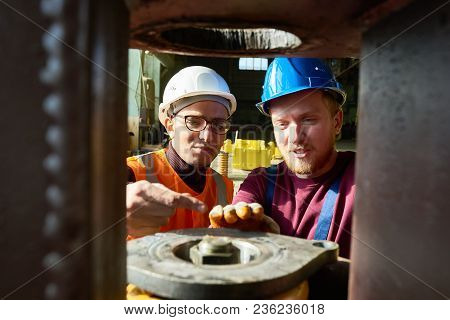 Multi-ethnic Team Of Worker Wearing Hardhats Making Necessary Adjustments To Machine While Standing