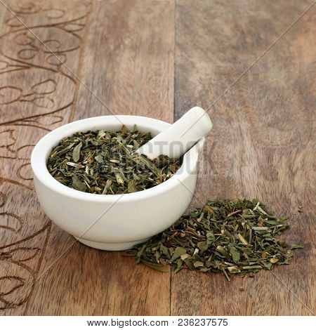 Rue leaf herb used in alternative herbal medicine to treat sprains, injuries of the cartilage & tendons around joints, sciatica and has other health benefits. In a mortar with pestle. Ruta graveolens.