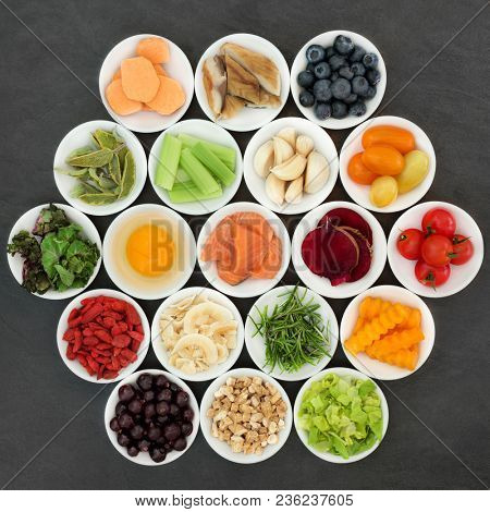 Brain boosting health food in porcelain bowls on slate background. Healthy food concept with foods high in omega 3 fatty acids, anthocynins, antioxidants, vitamins, minerals and fiber.
